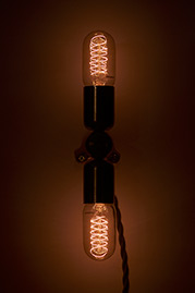 Doppio plug-in sconce with brass sockets, black cord, and Edison bulbs