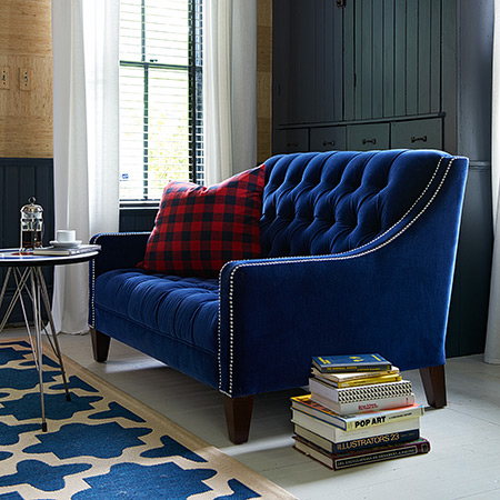 Blue velvet tufted Lincoln loveseat. Photo by Alec Hemer.