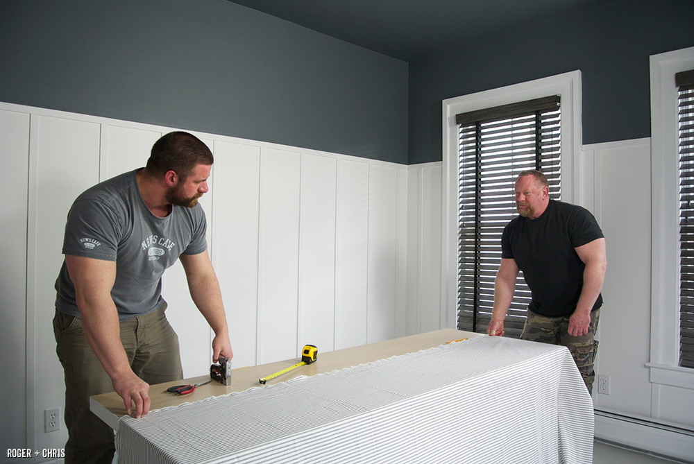 Chris and Roger apply fabric to the painted headboard.
