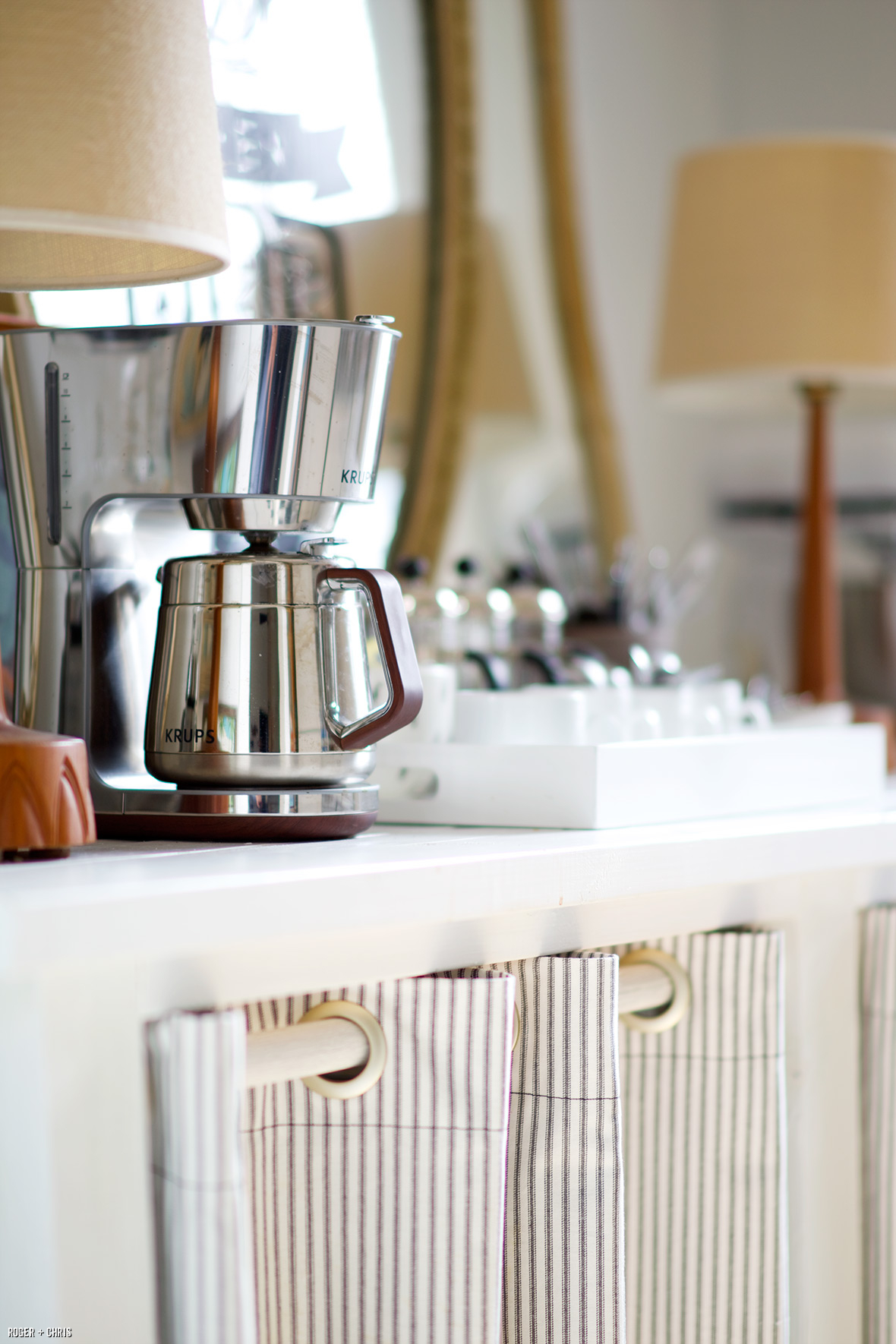 The coffee maker and cups sit atop the pantry table.