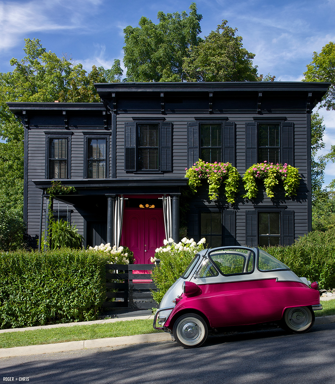 The front of the house with pink doors, window boxes, and a BMW Isetta parked out front.